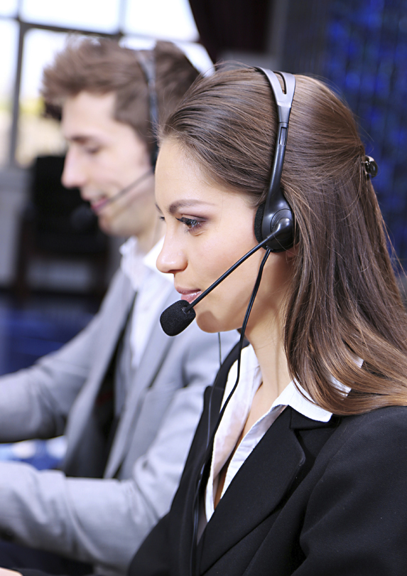 A woman working in customer service sits wearing headphones