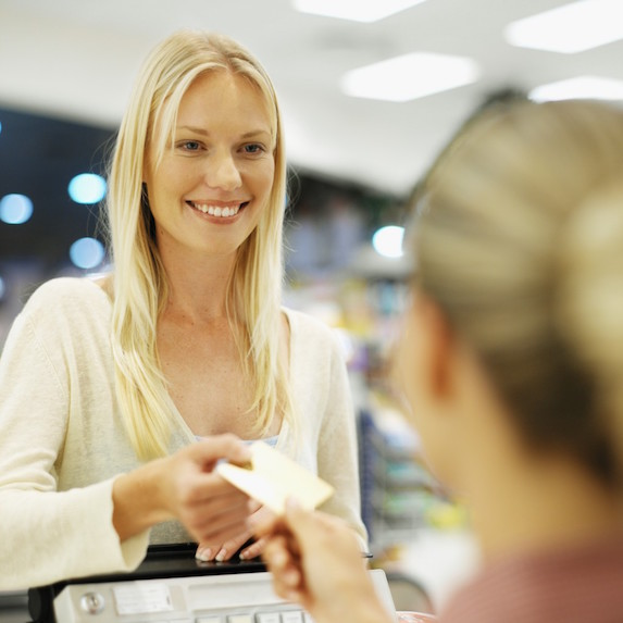 A smiling blonde woman hands over a credit card to pay while making a purchase
