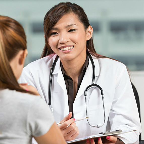A doctor in a lab coat with a stethoscope sits smiling and talking to a patient in front of her