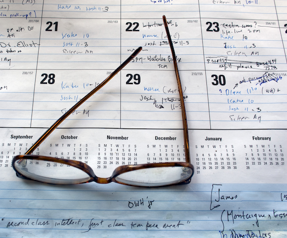 A pair of reading glasses lies on top of a filled-in calendar sheet