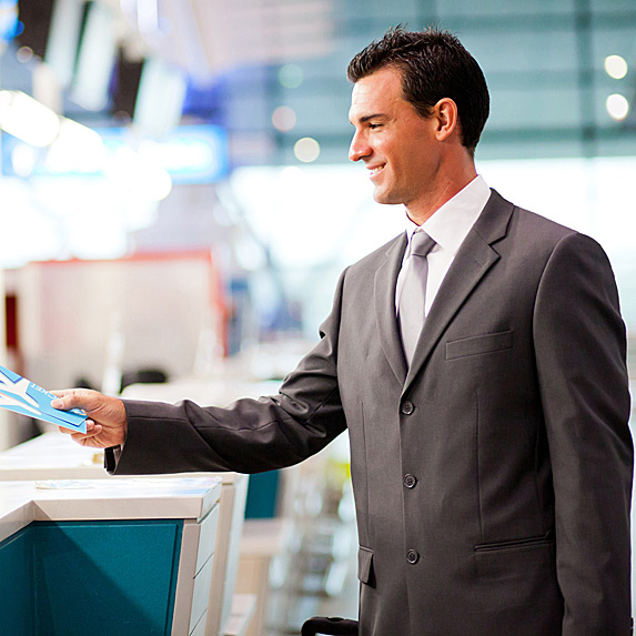 A man in a suit smiles as he accepts his travel documents over the counter at the airport