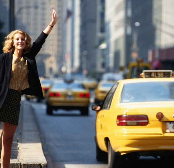 A woman flags down a cab on a city street