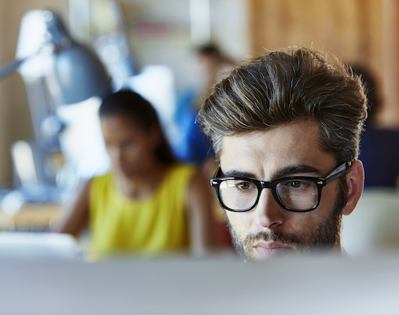 A man in glasses looks at a computer screen