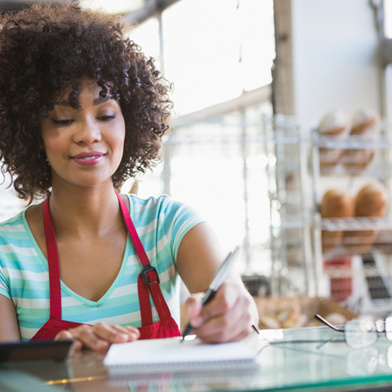 A young woman in an apron in a food establishment stands behind a counter making notes on a clipboard