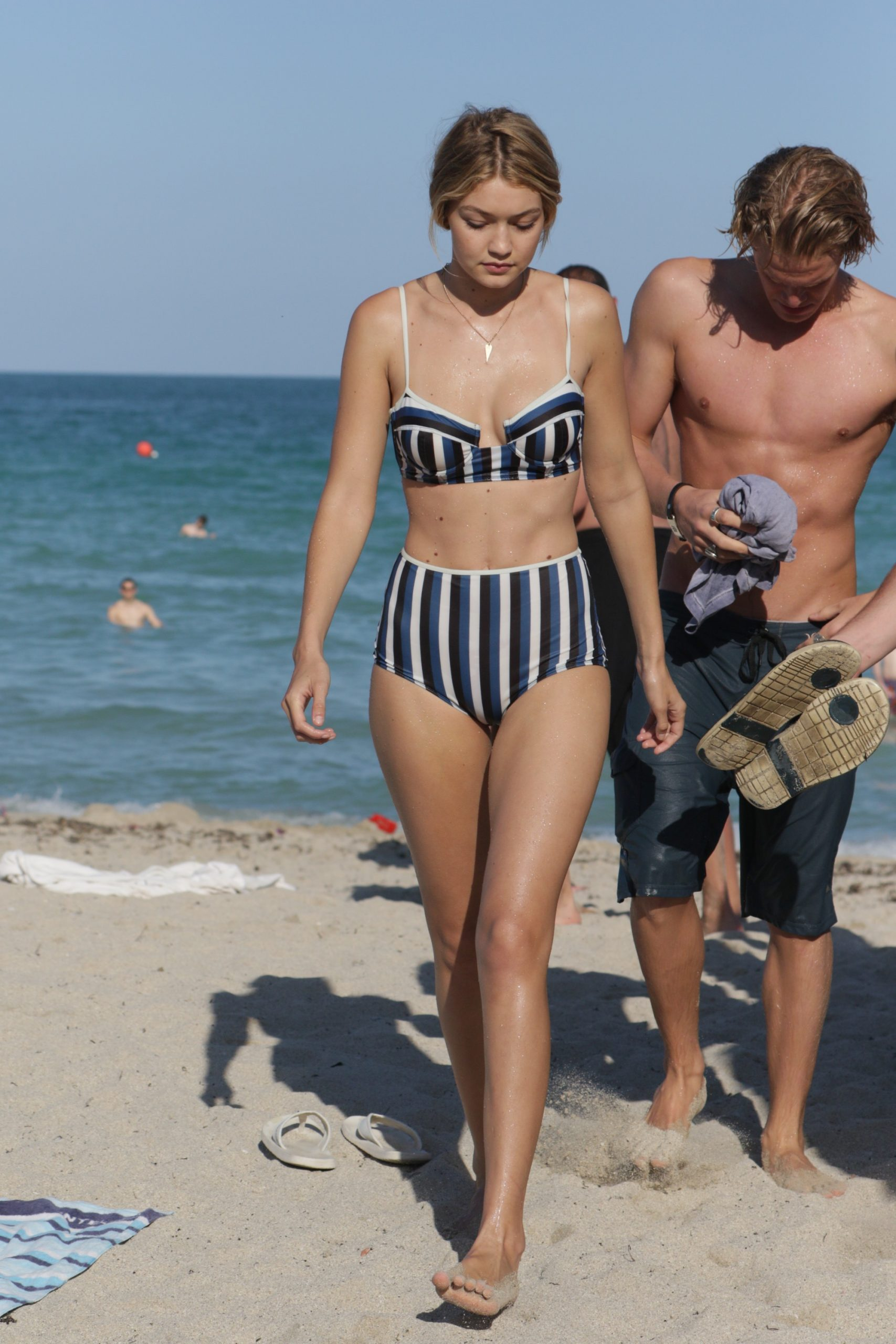 Model Gigi Hadid walks along the beach in a striped two-piece swimsuit