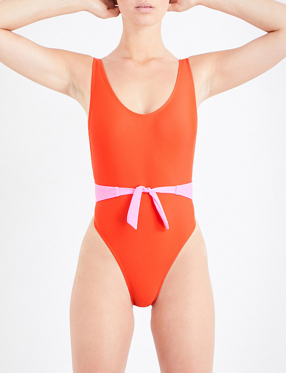 Model poses in a red and pink one-piece swimsuit with a front-bow feature