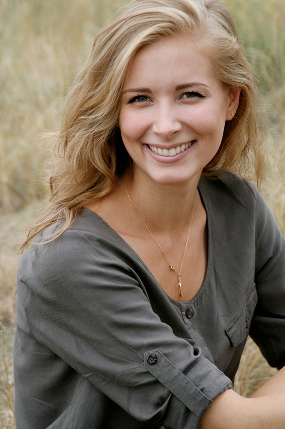 Pretty blond woman wearing a grey blouse and smiling while sitting outdoors.
