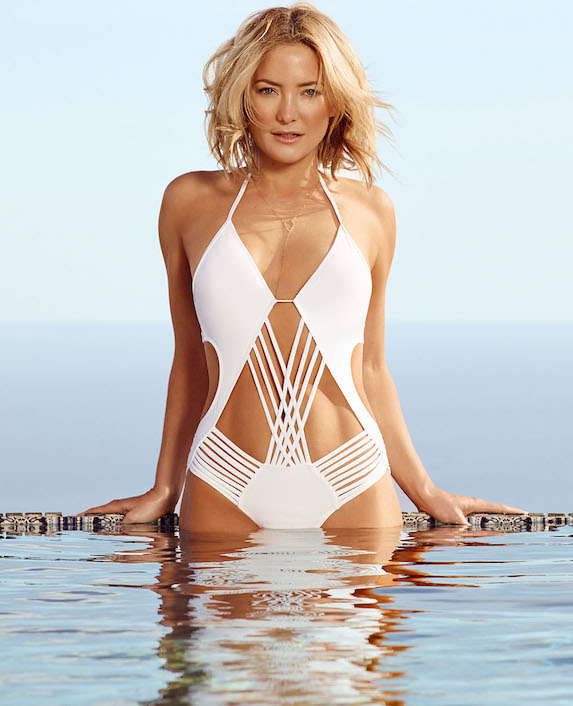 Kate Hudson poses in water wearing a white cut-out style one-piece swimsuit