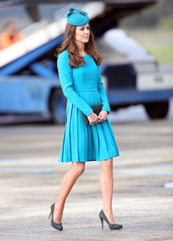 Kate Middleton is photographed in a bright blue dress with a pleated skirt detail by design brand Emilia Wickstead