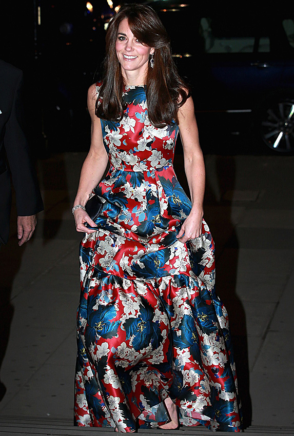 Kate Middleton smiles and holds up the full skirt on her floor-length floral gown
