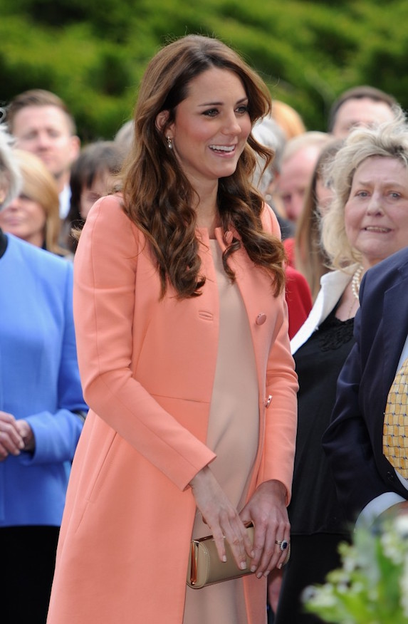 Kate Middleton wears pink overcoat and dress while holding a small cutch in front of her at an event