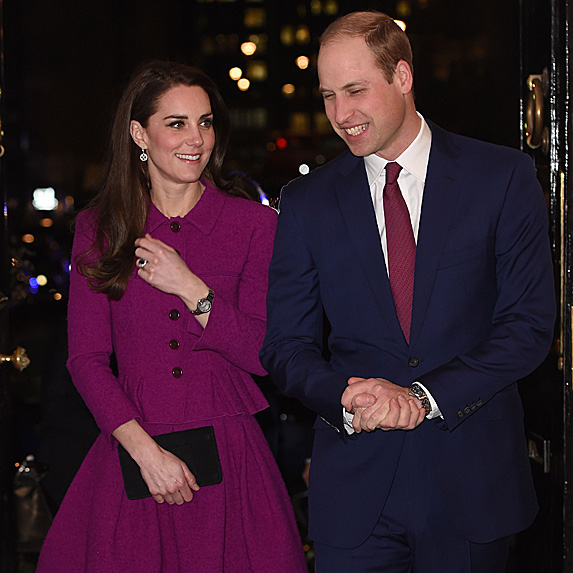 Kate Middleton smiles and looks to her husband William, as she holds a black clutch and dons a plum-coloured outfit by Oscar de la Renta
