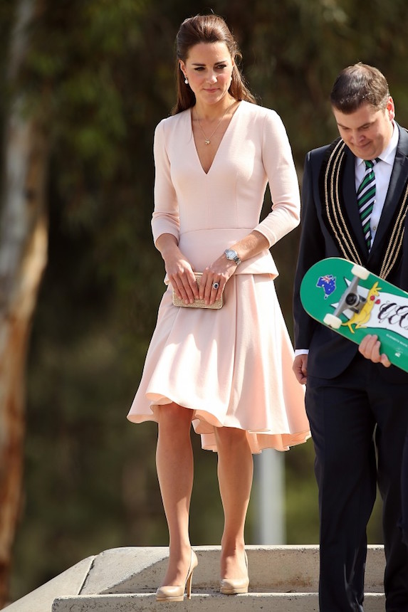 Kate Middleton holds a small purse in front of her while wearing a blush-pink dress