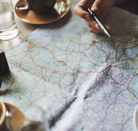 A hand points with a pen at a map laid open on a table