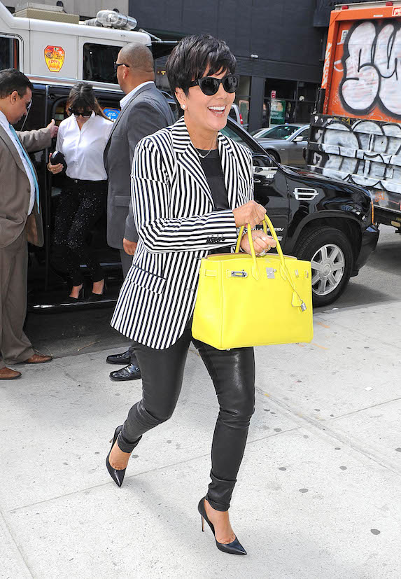 Kris Jenner spotted in leather leggings, a striped blazer, dark sunglasses and yellow designer bag