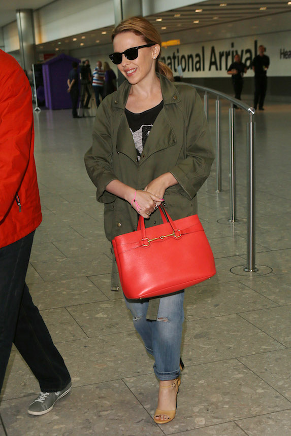 Singer Kylie Minogue smiles as she walks through the airport in sandals, jeans, a green overcoat and bright red designer bag.