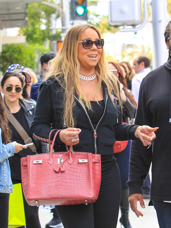 Candid photo of singer Mariah Carey amidst fans wearing a casual black tracksuit, flashy diamond necklace, sunglasses and a red designer handbag