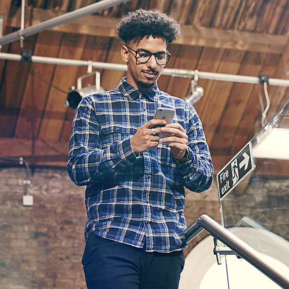 A young man in a flannel shirt walks while looking down his cell phone in his hands