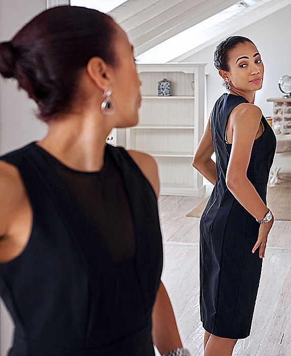 Woman trying on black dress in mirror