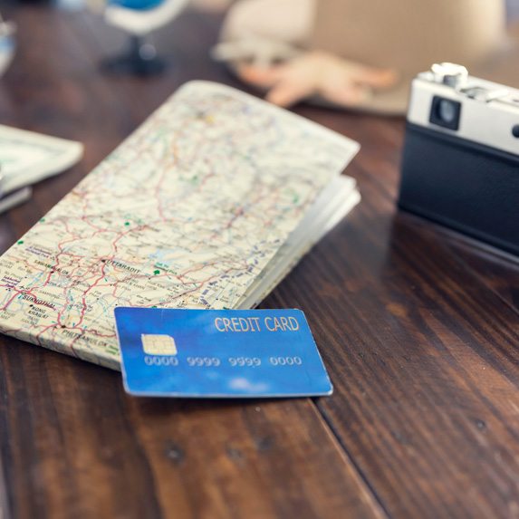 A blue generic credit card, a camera and a map on a table