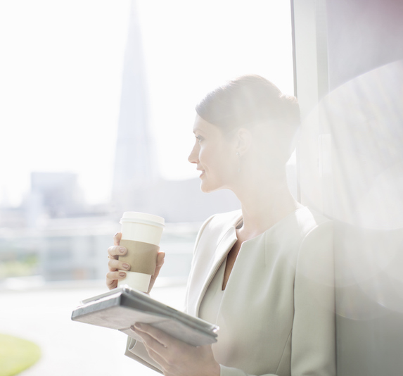 A woman holding a coffee and paperwork looks out a sunny window from within a building