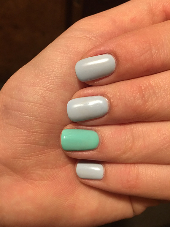 A woman's beautifully polished light grey nails with the ring fingernail mint green.
