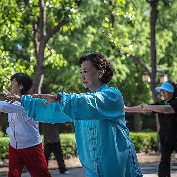 Three older women doing tai chi