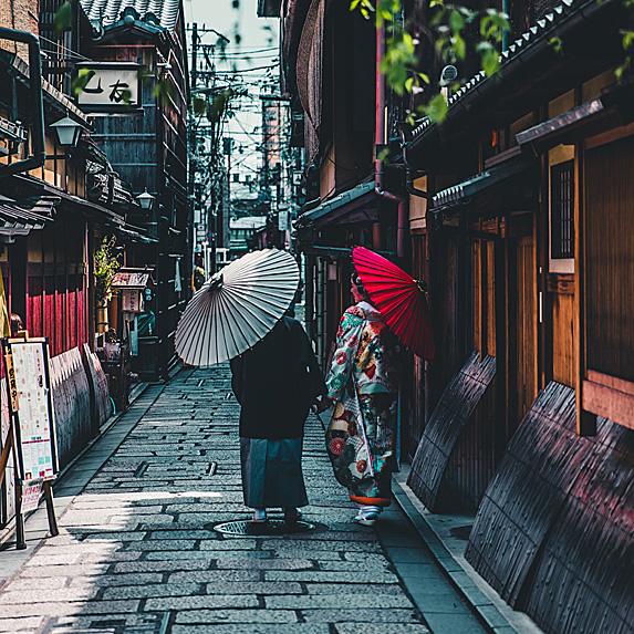 Two Japanese women walking down a street
