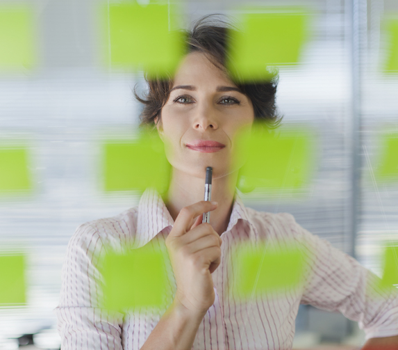 A smiling businesswoman examines several green post-it's posted up on a glass wall