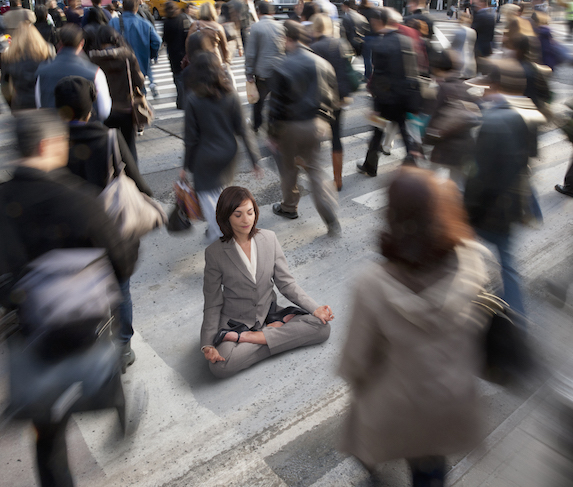 A brunette businesswoman sits cross-legged on a busy intersection amidst a blurred crowd of people passing by