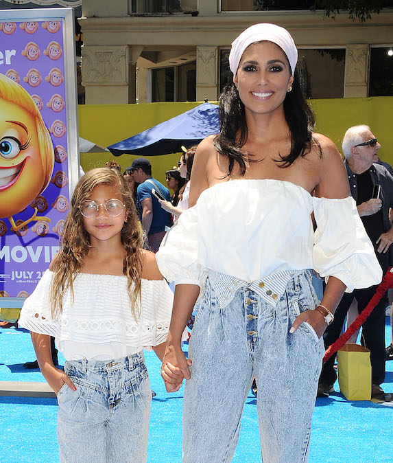 Designer Rachel Roy and daughter Tallulah Ruth hold hands at a red carpet premiere, dressed in matching denim and white blouses