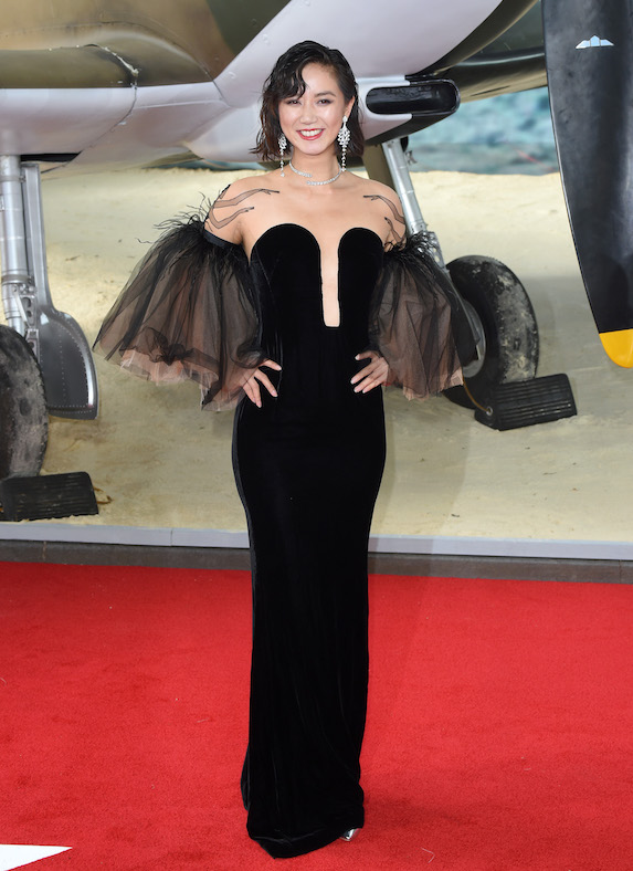 Betty Bachz wears a black low-cut gown with voluminous, exaggerated sleeves with feather details