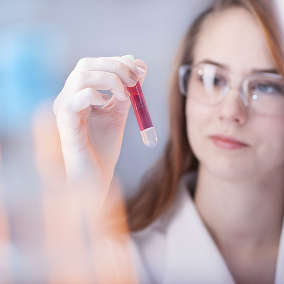A scientist wearing lab glasses examines a small glass vial of pink liquid in her hand