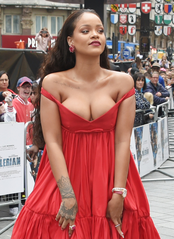 Rihanna attends a red carpet event wearing a red gown with a low neckline