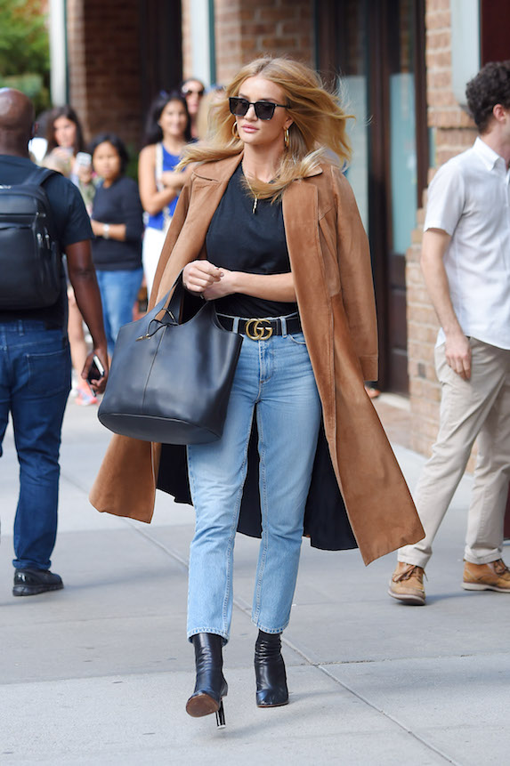 Rosie Huntington-Whiteley wearing black boots worn under blue jeans, a camel coat and Gucci belt