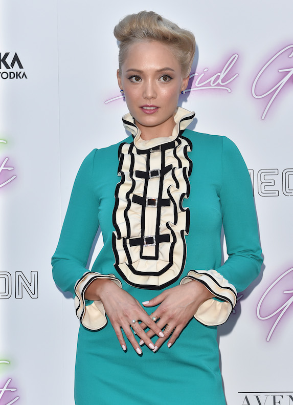Actress Pom Klementieff on the red carpet for a film premiere wearing a bright green dress with a black and white ruffled bib detail with a high neck