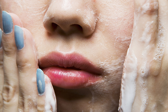 Young woman washing face, close-up of mouth
