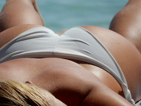 Tanned woman lying on her front on the beach wearing grey bikini bottoms.