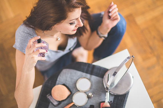 From above, a woman sitting in front of a portable mirror with cosmetics spread in front of her, spraying perfume onto herself.