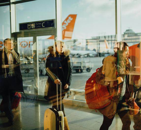 Travellers walk through an airport
