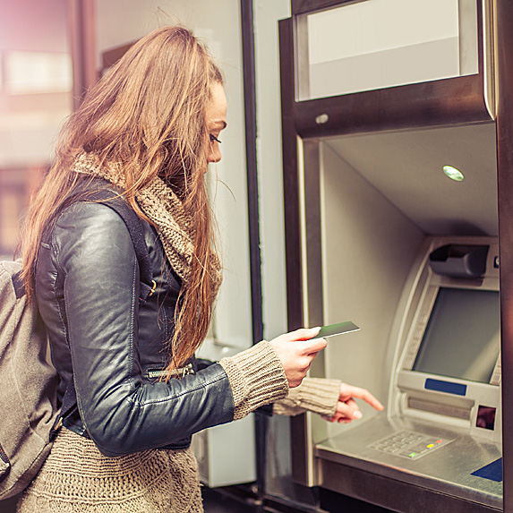 A young woman takes money out of an ATM machine