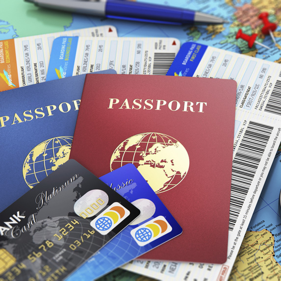 Credit cards, a passport and tickets for travel sit atop of an open map