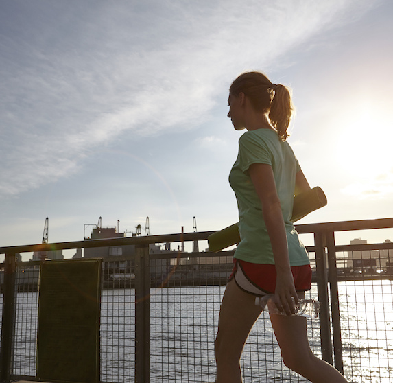 A young woman in athletic-wear and a ponytail walks along a pier holding a water bottle and yoga mat