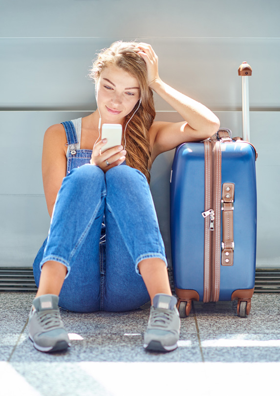 A young blonde woman sits on the ground with her suitcase at the airport, looking down at her phone