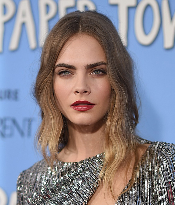 Cara Delevingne, from shoulders up, wearing a silver top and red lipstick with her wavy blond hair parted in the middle.