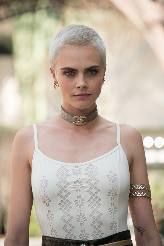 Cara Delevingne with platinum blonde, shaved hair, wearing a white tank top and Chanel choker.
