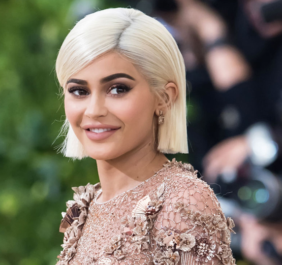 Kylie Jenner attends the 2017 Met Gala in May wearing a gold dress and short blonde hair