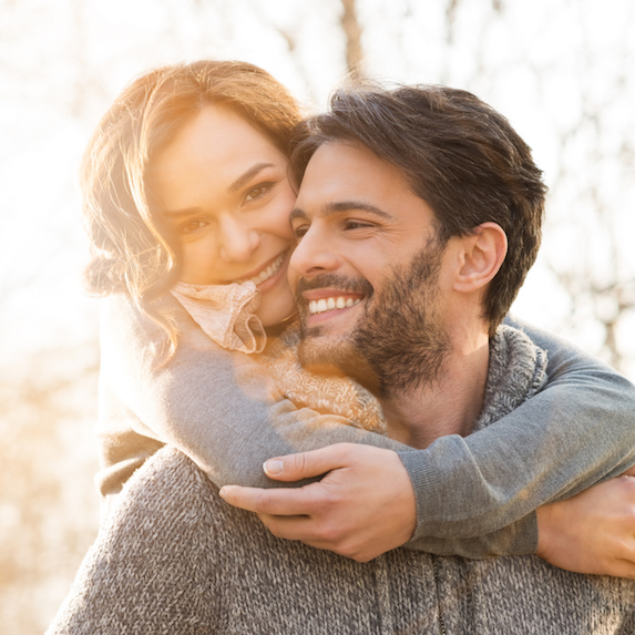 A smiling woman embraces a man around his shoulders from behind, as he looks towards her