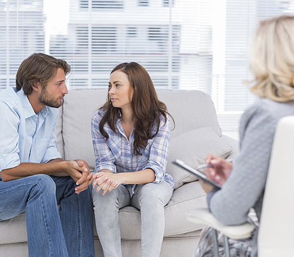 A couple sit, turned toward one another and holding hands, on a couch while a therapist looks on with a notepad and pen in hand