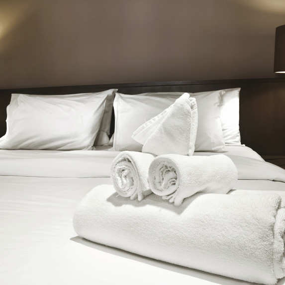 A neatly made bed with white bedding and rolled towels in a hotel room